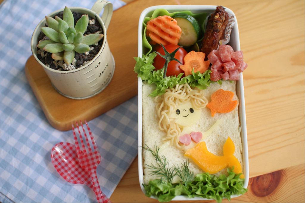 Does your little girl dream of transforming into a little mermaid? Learn the steps to craft this mermaid under the sea. In this bento, noodles are used for her soft, wavy hair. There are also instructions in this bento tutorial on how to make a ham flower, which serves as both filler and decoration for your bentos.