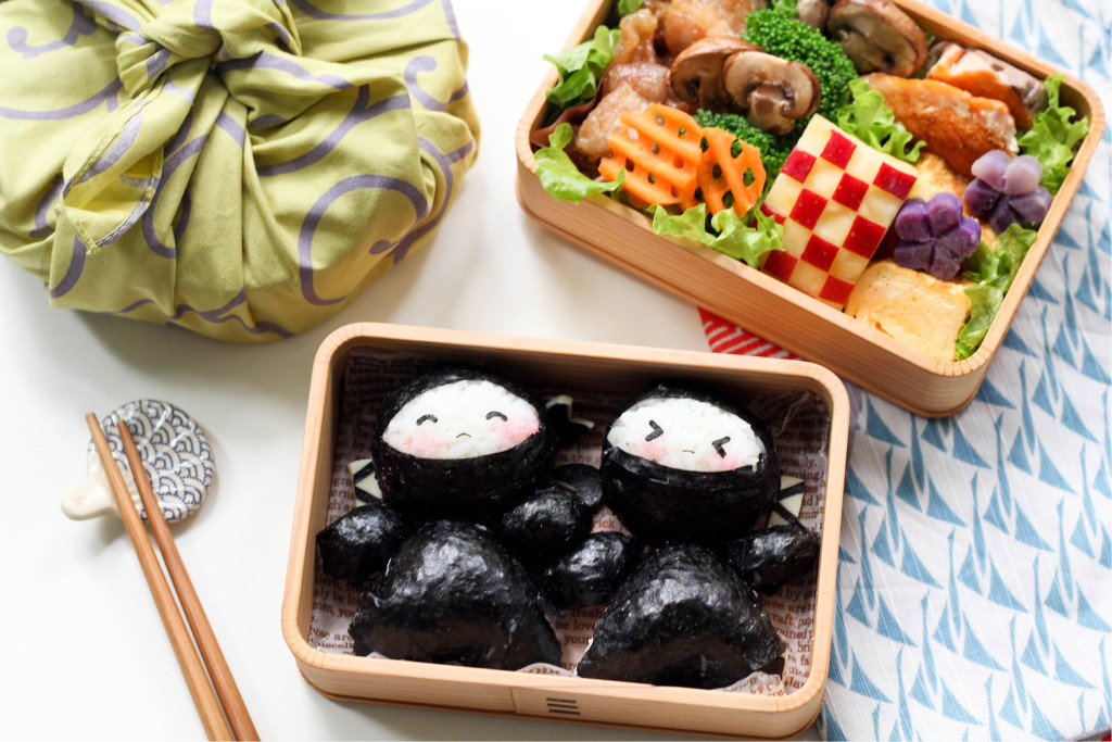 The boys will be thrilled to bring this cool ninja bento box to school, and even the girls would love these cute-looking ninjas! Nori is the perfect ingredient to make the ninja's outfit. Sakura denbu, a pinkish fluffy flaked fish condiment usually used in sushi rolls, is used to flush the ninja's cheeks. Sakura denbu can be bought in packets in Japanese supermarkets or online; otherwise a suitable substitute would be to use pink cake decorating gel.